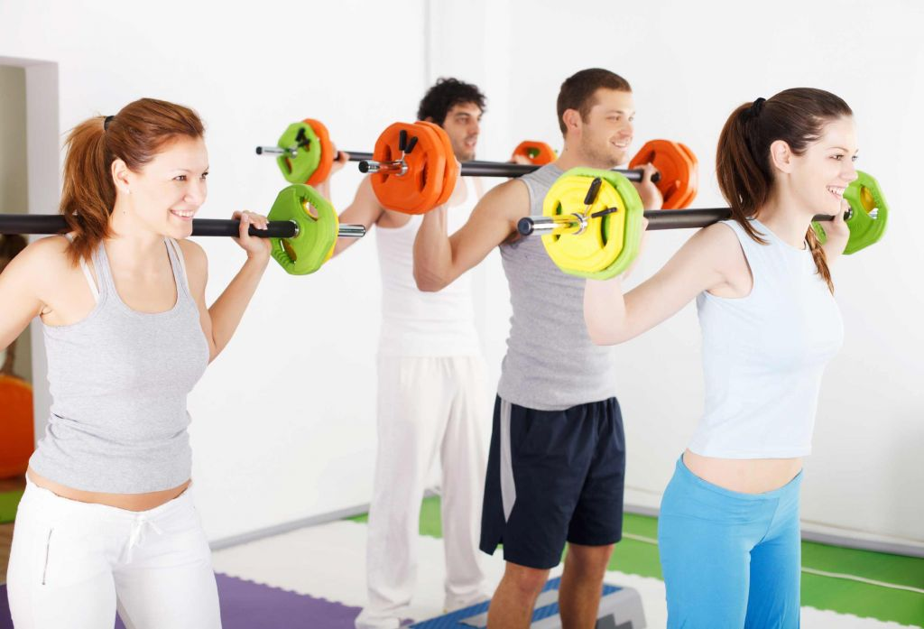 Group of people lifting barbells in weight training class.